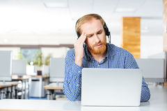 Man with headset and laptop suffering from headache on workplace Royalty Free Stock Photo