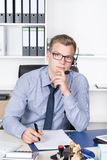 Man with headset is making notes in a file Royalty Free Stock Photography