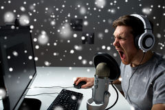 Man in headset playing computer video game at home. Technology, gaming, entertainment, let`s play and people concept - angry screaming young man in headset with Royalty Free Stock Photos