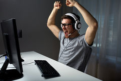 Man in headset playing computer video game at home Royalty Free Stock Photo