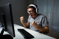 Man in headset playing computer video game at home. Technology, gaming, entertainment, let's play and people concept - happy young man in eyeglasses with headset Royalty Free Stock Image