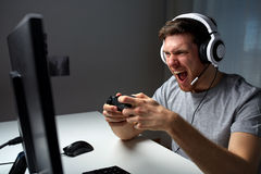 Man in headset playing computer video game at home. Technology, gaming, entertainment, play and people concept - angry screaming young man in headset with Royalty Free Stock Photos