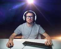 Man in headset playing computer video game. Technology, gaming, entertainment, let's play and people concept - young man in headset and eyeglasses with pc Stock Images