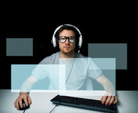 Man in headset playing computer video game Stock Photography