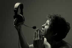 A man with a headset says softly into the microphone Royalty Free Stock Images