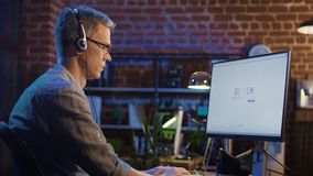 Man in headset surfing Internet in office Stock Photo