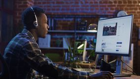 Man in headset surfing Internet in office stock images