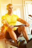 Man in health club exercise on row machine Royalty Free Stock Image
