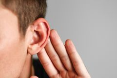 Man with hearing problem on grey background. Close up.  stock photography