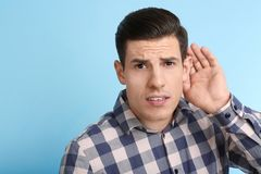 Man with hearing problem. On color background Royalty Free Stock Photo