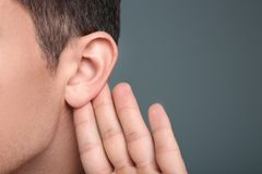 Man with hearing problem. On grey background, closeup Stock Image