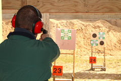 Man with hearing protection shooting gun at pistol range Royalty Free Stock Image