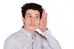 Man hearing something. Portrait of attractive young man hearing something. Isolated white background stock image