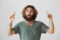 Man hears his favorite song playing by street band. Portrait of pleased handsome eastern man with beard and curly hair. Looking and pointing up with raised Royalty Free Stock Photo