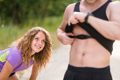 Man with heart rate monitor around chest. Tired woman athlete looking at him. Royalty Free Stock Photography