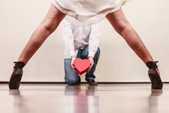 Man with heart shaped gift box for woman. Man guy holding heart shaped present gift box for hot women girl in high heels. Valentine day love concept royalty free stock photography