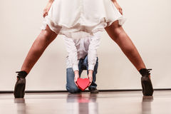 Man with heart shaped gift box for woman. Man guy holding heart shaped present gift box for hot women girl in high heels. Valentine day love concept stock photography