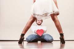 Man with heart shaped gift box for woman. Man guy holding heart shaped present gift box for hot women girl in high heels. Valentine day love concept royalty free stock image