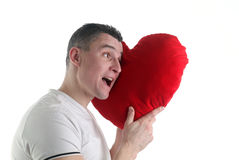 Man with a heart shaped pillow Royalty Free Stock Images