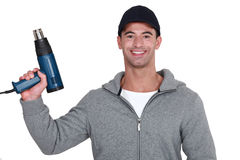 Man with a heat gun. In his hand Stock Photography