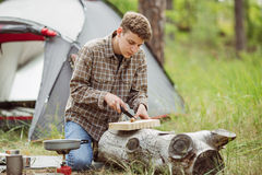 Man are heated in a fire and cook out on a summer forest Stock Photography