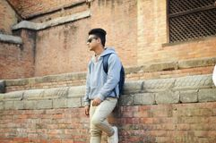 Man in Heather-grey Pullover Hoodie and Beige Pants Standing Near Brick Wall Royalty Free Stock Photo