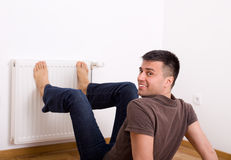 Man heating feet on radiator Stock Photography