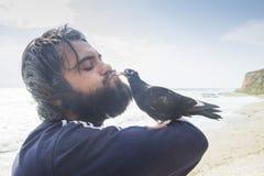 Man kissing pigeon. Bondage between man and pigeon Royalty Free Stock Image