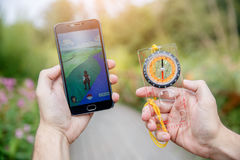 Man held in hands compas and phone showing its screen with Pokemon Go application. Man held in hands compas and phone showing its screen with Pokemon Go royalty free stock photos