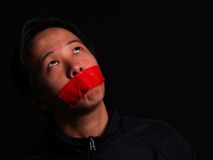 A man held hostage. An Asian man held hostage with red tape over his mouth Stock Photo