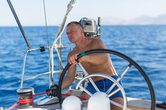 Man at the helm sail boat Royalty Free Stock Photography