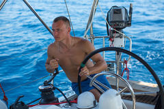 Man at the helm sail boat, the ship controls during sea yacht race. Stock Images