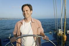 Man at helm of sailboat Stock Photo