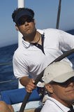 Man At The Helm Of A Sailboat In The Ocean Stock Images