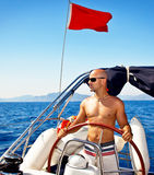 Man at the helm of yacht Stock Photo