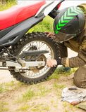 Man adjusting bolts with socket wrench on rear motorcycle wheel. Man in helmet adjusting bolt with socket wrench on rear motorcycle wheel. Bike rider fixing his stock photography