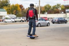 Man with helmet and backback on one wheel motorized skateboard on sidewalk in urban area with cars on stree and stores and fall. Trees in background - selective royalty free stock photo