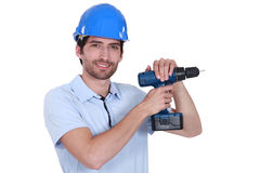 Man with helmet and drill Stock Images