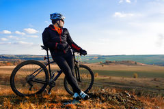 Man in helmet and glasses stay on the bicycle under sky with clouds. Royalty Free Stock Image