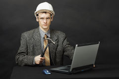 Man in helmet with hammer repairs computer Royalty Free Stock Image