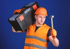 Man in helmet, hard hat carries toolbox and holds hammer, blue background. Handyman concept. Worker, repairer, repairman. Builder on calm face carries toolbox royalty free stock photography