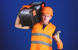 Man in helmet, hard hat carries toolbox and holds hammer, blue background. Worker, repairer, repairman, builder on calm. Face, handyman with hammer carrying stock photo