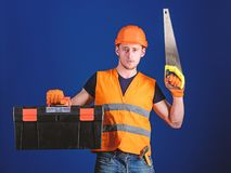 Man in helmet, hard hat carries toolbox and holds handsaw, blue background. Carpenter concept. Worker, repairer. Repairman on serious face carries toolbox stock photo