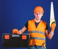 Man in helmet, hard hat carries toolbox and holds handsaw, blue background. Worker, repairer, repairman on serious face. Carries toolbox, ready for repair, copy royalty free stock photography
