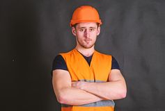 Man in helmet, hard hat hold arms crossed on chest, black background. Worker, contractor, builder on strict face with. Muscular biceps. Strong builder concept royalty free stock photography