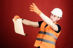 Man in helmet, hard hat holds building plan, controls works, red background. Architect concept. Engineer, architect. Builder on strict face holds old blueprint royalty free stock images
