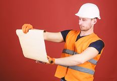 Man in helmet, hard hat holds building plan, controls works, red background. Engineer, architect, builder on strict face. Holds old blueprint in hands stock photos
