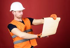 Man in helmet, hard hat holds building plan, controls works, red background. Engineer, architect, builder on strict face. Holds old blueprint in hands Royalty Free Stock Image