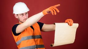 Man in helmet, hard hat holds building plan, controls works, red background. Foreman concept. Engineer, architect. Builder on strict face holds old blueprint royalty free stock photos