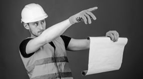 Man in helmet, hard hat holds building plan, controls works, red background. Foreman concept. Engineer, architect. Builder on strict face holds old blueprint royalty free stock image